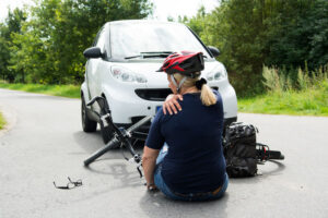 Woman and her bicycle on the ground after being hit by a car