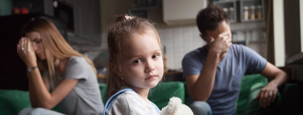This image shows a sad child as her parents argue behind her.