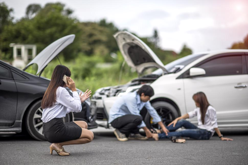 A man helping an injured woman after a car accident while another woman speaks on the phone.