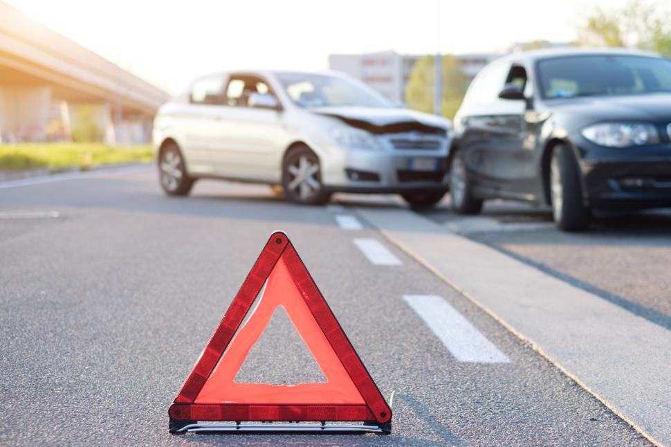 A cone placed in the road near a rear-end car accident.