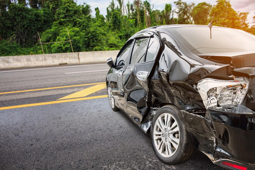 A heavily damaged car on a highway shortly after an accident.