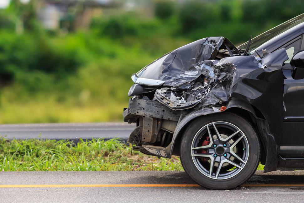 The heavily damaged front of a car resulting from an accident.