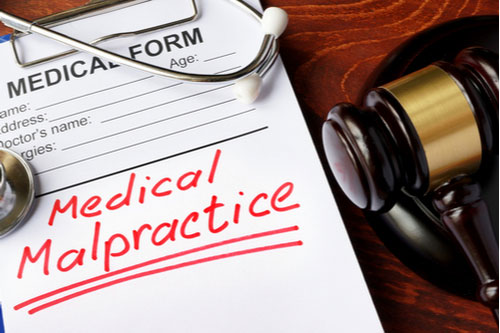 Medical form with words medical malpractice and gavel