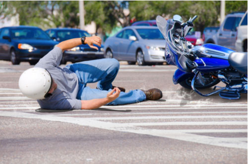 Motorcycle rider has wrecked and is laying in the road as his motorcycle slides into a busy intersection