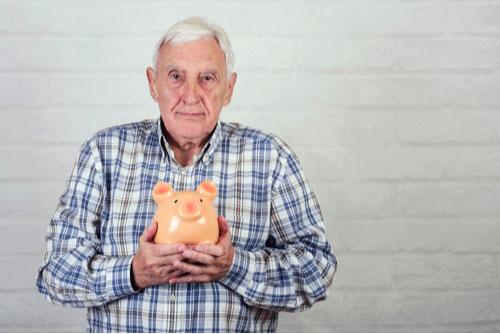Senior man holding piggybank, concept of financial exploitation