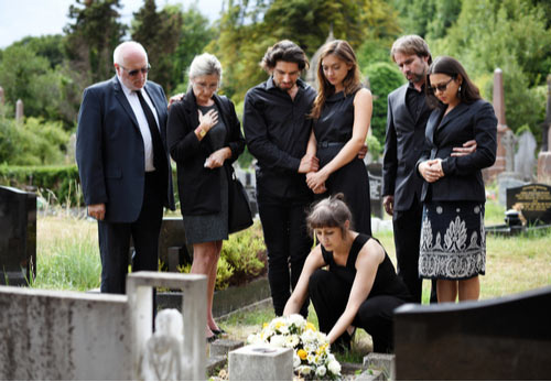 Family group placing flowers on a grave