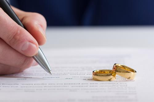 A person signing a divorce form.